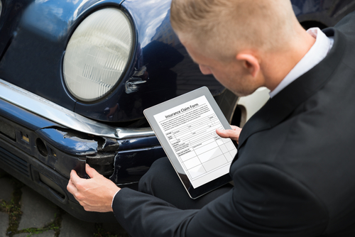 insurance agent inspecting car