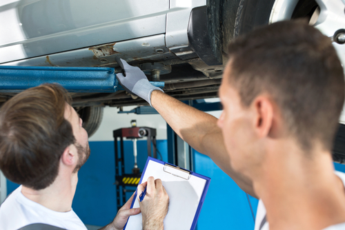 mechanics showing defect on car