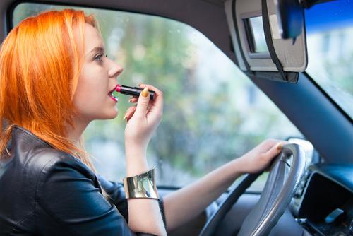 woman applying makeup in car