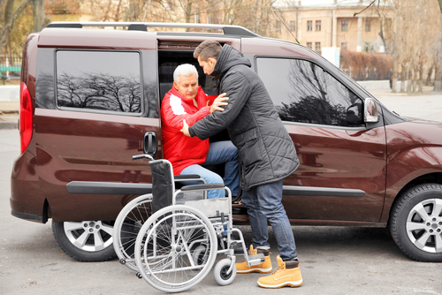man helping handicapped man in wheelchair