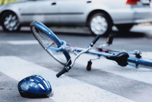 helmet and bike lying on road
