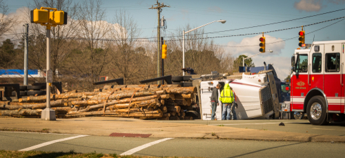 overturned logging truck in intersection